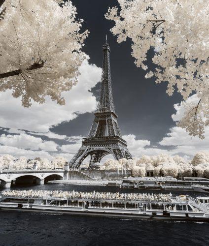 Tour Eiffel à travers les arbres et péniche naviguant sur la Seine. Photographie infrarouge issue de la série Paris Invisible et réalisée par le photographe Pierre-Louis Ferrer, spécialiste en photographie dans l'ultraviolet et l'infrarouge.