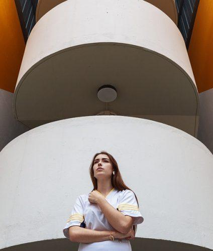 Portrait au grand angle d'une modèle en contre-plongée devant une façade urbaine.