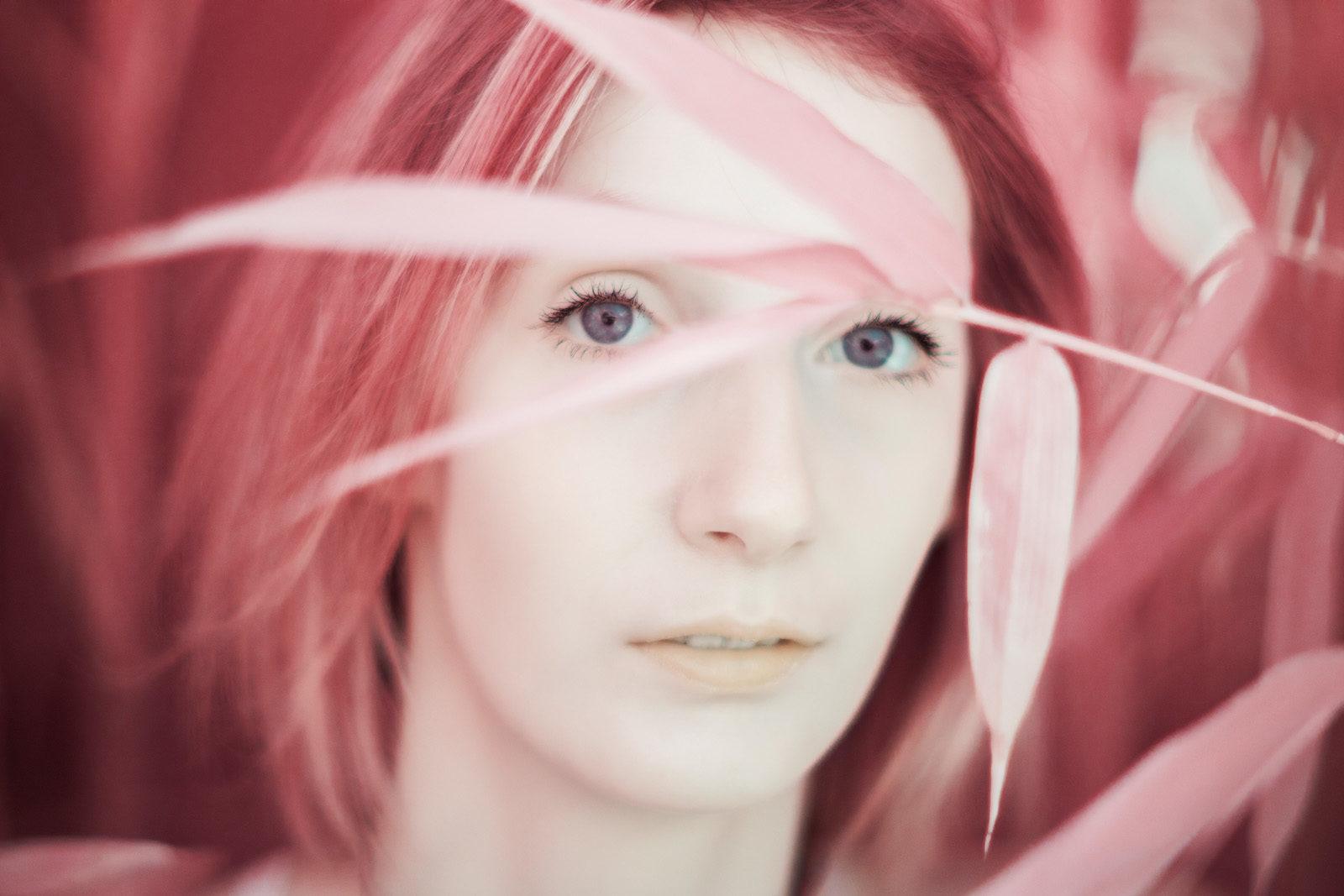Portrait en infrarouge aerochrome numérique d'une jeune fille dont le visage est caché derrière des feuilles de bambou.