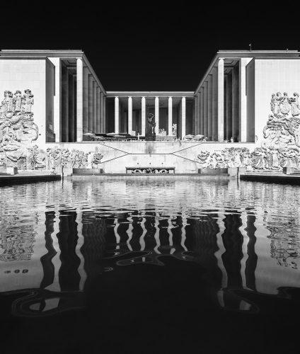 Façade du Palais de Tokyo et reflexion texturée dans le bassin. Photographie d'architecture en noir et blanc de Pierre-Louis Ferrer.