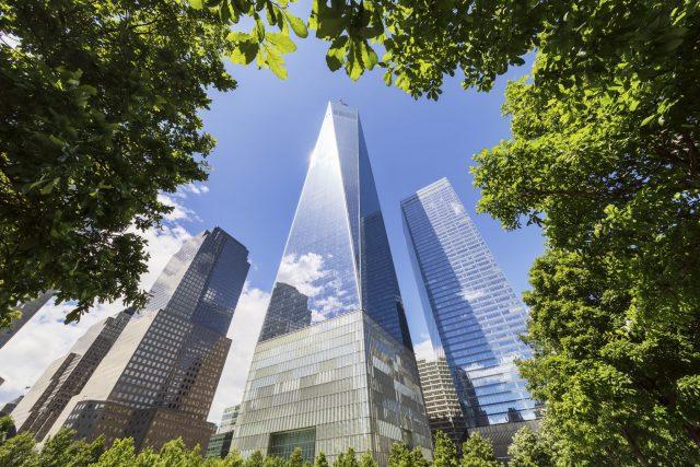 One World Trade Center à travers les arbres du mémorial de New York. Photographie d'architecture réalisée par le photographe Pierre-Louis Ferrer, spécialiste en photographie dans l'ultraviolet et l'infrarouge.