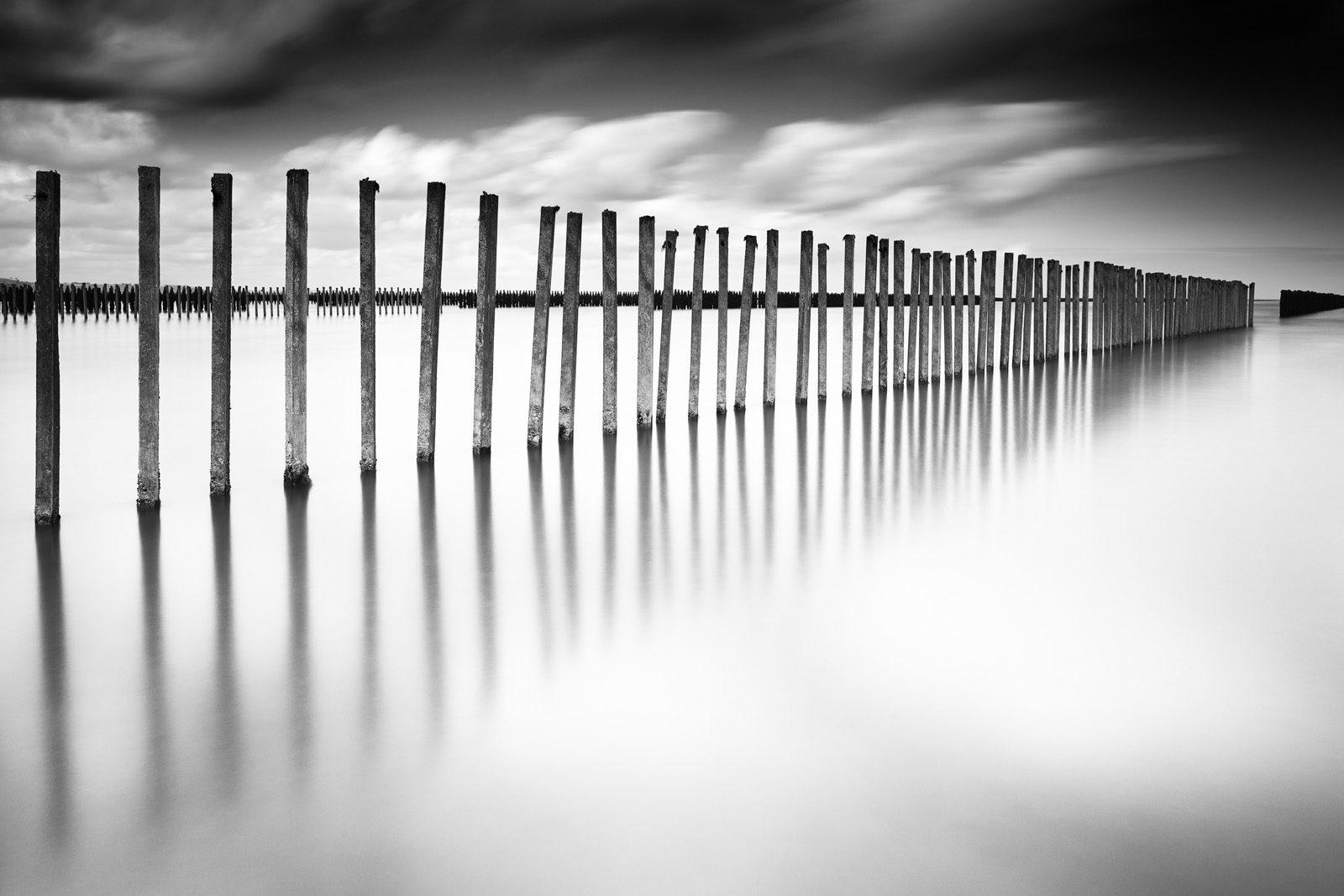 Paysage marin en noir et blanc et pose longue présentant une perspective de piquets de bouchots dans l'eau. Photographie réalisée par le photographe Pierre-Louis Ferrer, spécialiste en photographie dans l'ultraviolet et l'infrarouge.