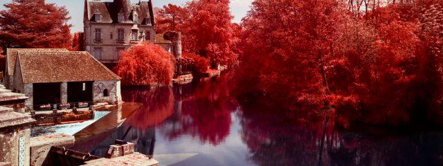 MMoulin de Moret sur Loing entouré de végétation rouge. Photographie en infrarouge réalisée par Pierre-Louis Ferrer.