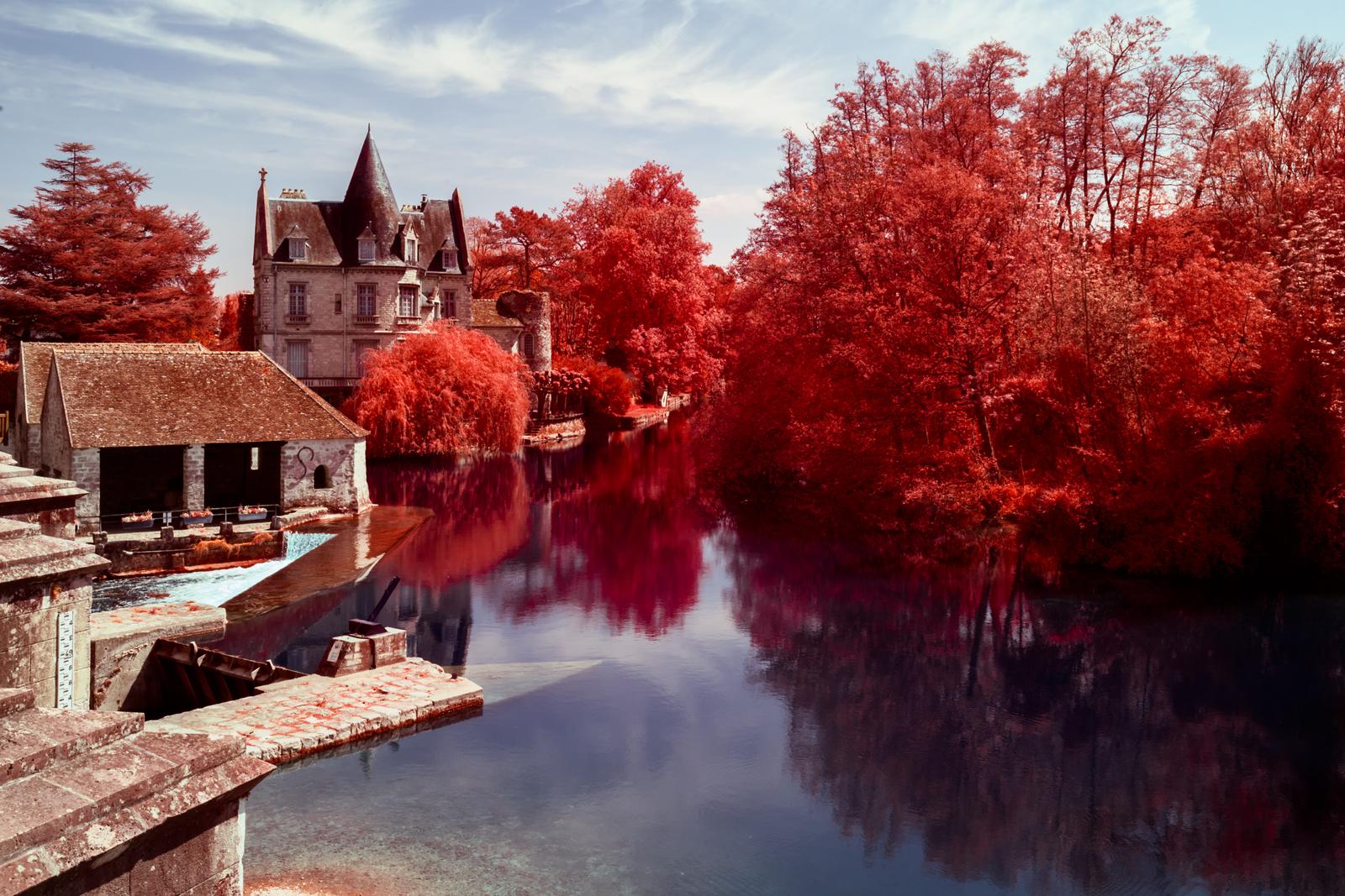 Résultat final d'un traitement en aerochrome numérique, présentant le moulin de Moret sur Loing entouré de végétation rouge. Photographie en infrarouge réalisée par Pierre-Louis Ferrer.