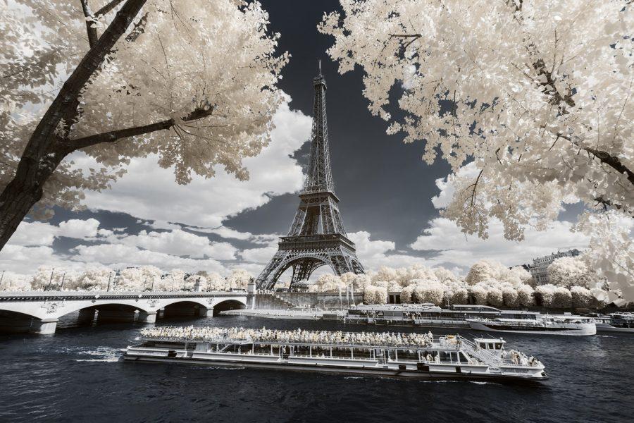 Tour Eiffel à travers les arbres et péniche naviguant sur la Seine. Photographie infrarouge issue de la série Paris Invisible et réalisée par le photographe Pierre-Louis Ferrer, illustrant le workshop photographie infrarouge.